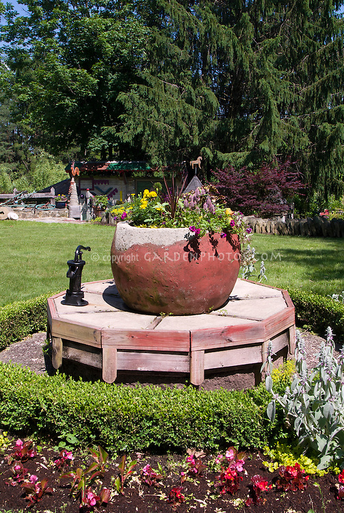 Huge Container Planter As Focal Point In Garden On Raised Platform Well  Pump, Lawn Grass