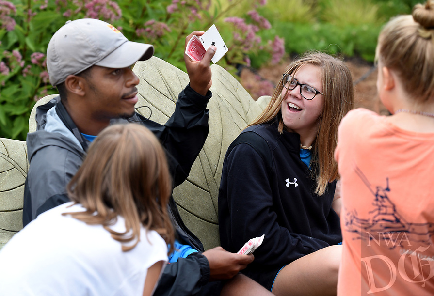 NWA Democrat-Gazette/DAVID GOTTSCHALK Katie Kieklak (right), a junior camp counselor, reacts to a card trick Thursday, August 8, 2019, by Warrington Sebree, camp counselor, during during the city of Fayetteville's Parks and Recreation Department Be Active! Camp Wilson at Wilson Park in Fayetteville. Campers participated in volleyball, tennis, swimming and a dance off during the week long half day camp that concludes today.