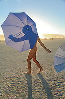 Naked man with umbrella. Burning Man is an eight-day annual event that takes place in Black Rock City, a temporary city on the playa of the Black Rock Desert in the U.S. state of Nevada, 90 miles (150 km) north-northeast of Reno, ending on the American Labor Day holiday in September. The event is described by organizers as an experiment in community, radical self-expression, and radical self-reliance and takes its name from the ritual burning of a large wooden effigy on Saturday evening.