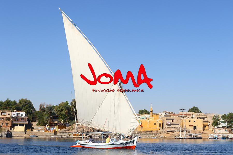 Traditional felucca sailing boat crossing Nile river at Aswan