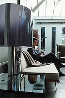 The owner of the loft apartment relaxing on a George Nelson banquette sofa next to a large metal and plexiglass table lamp placed on a Jacques Dumond metal and glass side table