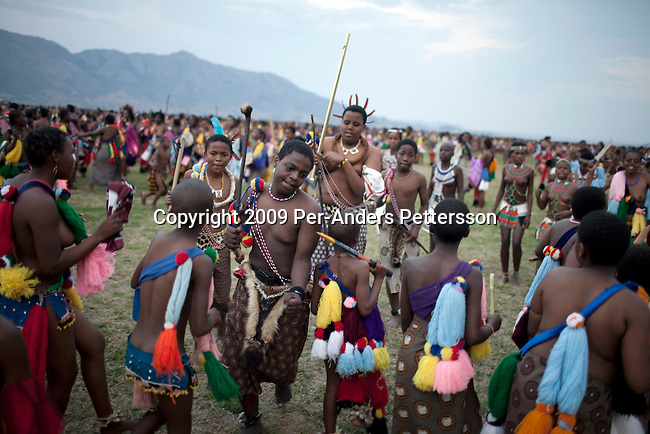 LUDZIDZINI, SWAZILAND - AUGUST 30: Children of King Mswati III dances in front of young virgins at a traditional Reed dance ceremony at the stadium at the Royal Palace on August 30, 2009, in Ludzidzini, Swaziland. About 80.000 virgins from all over the country attended this yearly event, the biggest in Swazi culture. It was founded to celebrate the beauty of Swazi women and girls. King Mswati III, and absolute monarch, was born in 1968 and he has 14 wives and many children. The king danced with his men in front of the 80.000 girls. Many of the girls hope to get noticed by the king and to be chosen as a future wife, a ticket from poverty and into a life of privilege and luxury. The country is one of the poorest in the world and it is struggling with a high prevalence of HIV-Aids and severe poverty. (Photo by: Per-Anders Pettersson)....