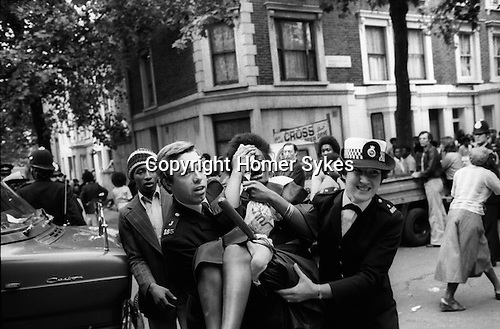 Notting Hill Gate Carnival race riot, London W11 England 1976. Young black girl who has been hit in the face by a missle is carried away from the trouble by the police.