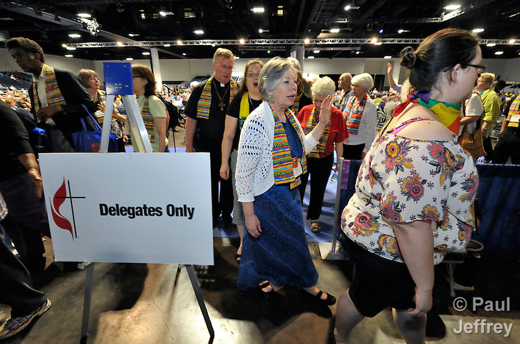 Dozens of demonstrators demanding a more inclusive church leave the floor of a May 3 session of the 2012 United Methodist General Conference in Tampa, Florida. They held communion around the center table and sang songs, causing the presiding bishop to suspend the morning session. The demonstrators left at the beginning of the afternoon session after discussion with several women bishops, who publicly told the demonstrators that they felt the pain they had experienced as a result of the conference's actions to continue the denomination's position on homosexuality.