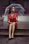 Young woman in a red elegant dress waiting for someone sitting on the stairs with an umbrella in the rain on a city street