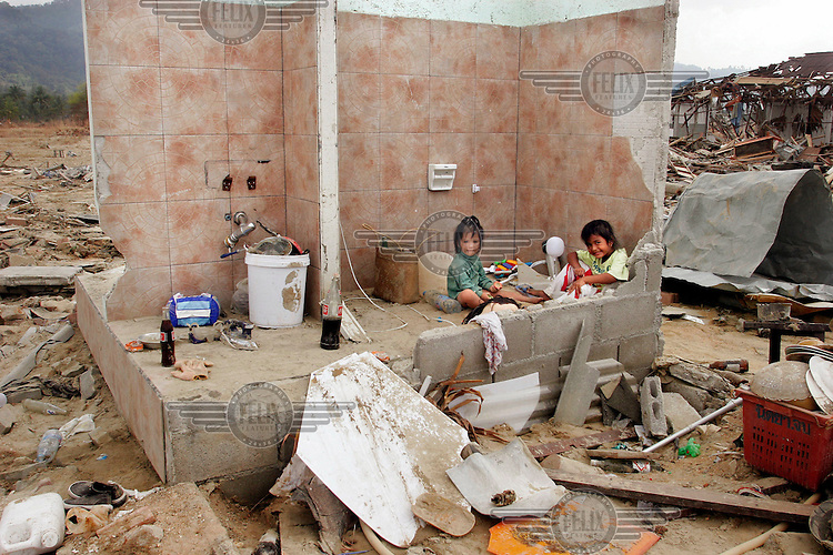 Two children play in the remains of their home, destroyed in the tsunami which struck South Asia on 26/12/2004. 