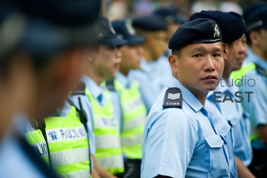 HONG KONG, HONG KONG SAR, CHINA - OCTOBER 13: Police officers form a cordon to prevent pro-democracy protesters to regain territory in front of Pacific Place shopping mall in Queensway, Admirality, Hong Kong, China, on October 13, 2014. Hundreds of men attempted to break through barricades erected by Hong Kong pro-democracy protesters near the city's business district, as a third week of rallies tried the patience of truck and cab drivers. 'Occupy Central' protesters came back and sit on the pavement to make sure Queensway stayed theirs. The 'Umbrella revolution' or 'Occupy Central' is a civil disobedience movement that began in response to China's decision to allow only Beijing-vetted candidates to stand in the city's 2017 election for the top civil position of chief executive. Thousands of pro-democracy supporters are calling for open elections and the resignation of Hong Kong's Chief Executive Leung Chun-ying. (Photo by Lucas Schifres/Getty Images)