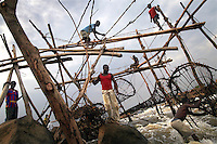 Fishermen position a fish trap into place on a wooden scaffold at Boyoma Falls (known locally as Wagenia Falls). This is the last of seven cataracts below which the Lualaba River becomes the Congo. For generations members of the Wagenia tribe have built and maintained these structures in the same manner described by Henry Morton Stanley, after whom the falls were also once named, during his navigation of the Congo in 1874-77.