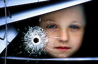 Following a loyalist gun attack in the Nationalist Short Strand area of Belfast, N Ireland, a child peers through the blinds and the bullet hole in her living room window. June 2002. 200206006571 <br />