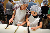 Learning to make chikuwa kamaboko at the kamaboko museum, Suzuhiro kamaboko, Odawara, Kanagawa prefecture, Japan, August 19, 2009.
