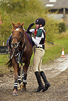 Young rider loosens his horse's girth after a cross-country competition, Highworth, United Kingdom