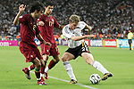 08 July 2006: Marcell Jansen (GER) (2 white) is challenged for the ball by Cristiano Ronaldo (POR) (17) and Deco (POR) (20, looks like 2 red). Germany defeated Portugal 3-1 at the Gottlieb-Daimler Stadion in Stuttgart, Germany in match 63, the third-place game, of the 2006 FIFA World Cup.
