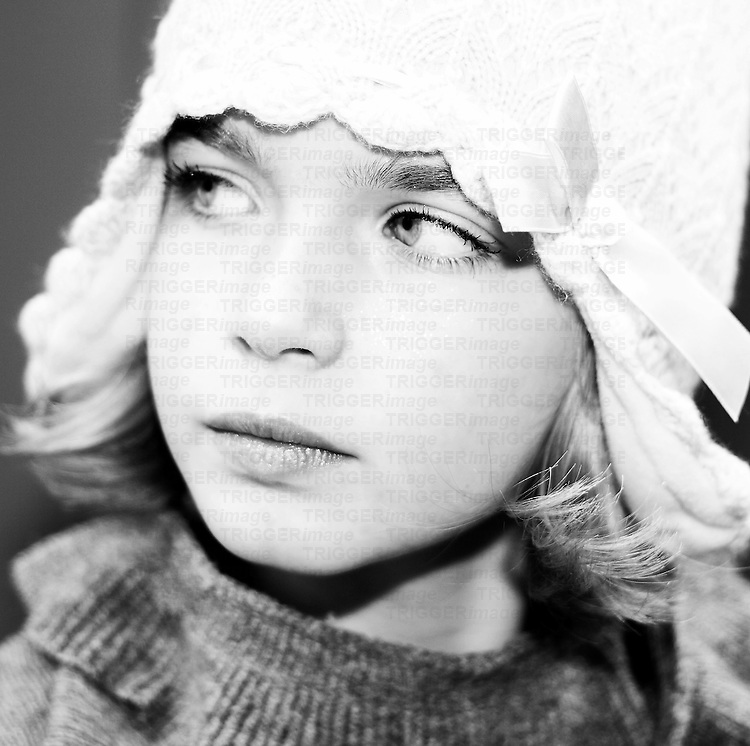 Young girl looking to one side wearing a hat with silk bow