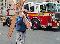 An FDNY fire truck on the way to a call passes the Franciscan Friars of the Renewal Way of the Cross Witness Walk on Good Friday, April 18, 2014 in Harlem in New York . The procession starts at St. Joseph's Friary in Harlem and ends several hours later at the St. Crispin Friary in the Bronx where a Good Friday service takes place. Several hundred parishioners as well as clergy participated in the event, part of Holy Week,  which commemorates the crucifixion of Jesus Christ. (© Richard B. Levine)