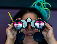 BALTIMORE, MD - MAY 20: A woman watches an undercard race through binoculars on Preakness Stakes Day at Pimlico Race Course on May 20, 2017 in Baltimore, Maryland.(Photo by Douglas DeFelice/Eclipse Sportswire/Getty Images)