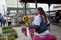A woman holding sunflowers walks in Detroit Eastern Farmers market in Detroit (Mi) Saturday June 8, 2013. The largest open-air flowerbed market in the United States, the Eastern Market is a historic commercial district in Detroit, Michigan.