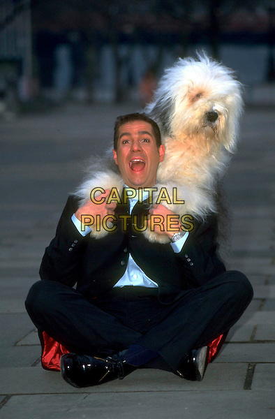 DALE WINTON.Ref: 2124.pre 2001.full length black suit sitting dog animal pet mouth open funny .CAP/RK.©RK/Capital Pictures.