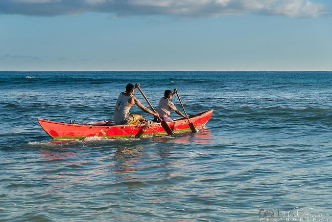 Paddling a traditional canoe on the island of Kiritimati in Kiribati.