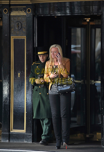 MICHELLE MONE.talking on her mobile phone outside her hotel, London, England, UK, .February 10th 2010..full length cell black bag handbag brown leather tan jacket jeans trousers christian louboutin shoes grey gray silver top .CAP/DYL.©Dylan/Capital Pictures.