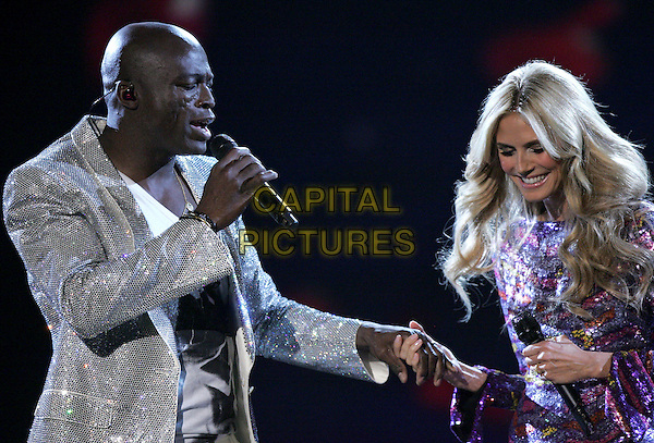SEAL & HEIDI KLUM.The 2007 Victoria's Secret Fashion Show held at The Kodak Theatre in Hollywood, California, USA..November 15th, 2007 .half length microphone married husband wife sequins sequined dress pink yellow silver holding hands singing silver stage concert live gig performance music .CAP/DVS.©Debbie VanStory/Capital Pictures