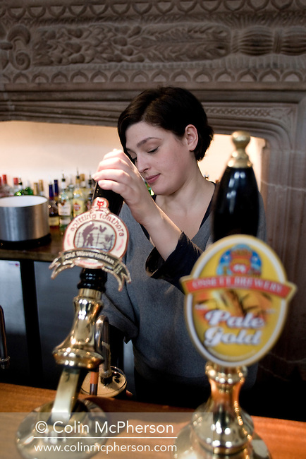 A pint of Old Wavertonian brewed by Spitting Feathers Brewery in Cheshire, being poured by a barmaid at the Brewery Tap public house in Chester, pictured as part of the Cheshire Food Trail. The bar was opened in November 2008 and is house in a former Jacobean mansion which dates back to the 17th century.