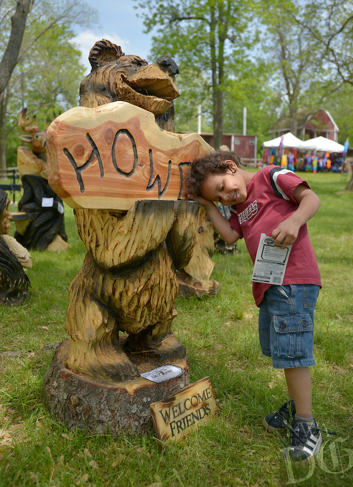 NWA Democrat-Gazette/BEN GOFF -- 05/03/15 Avionta Blackburn, 4, of Fayetteville checks out a carving by Jason Morton of Eagle Ridge Chainsaw Carving in Springfield, Mo. while visiting the Sharp's Show of War Eagle spring craft fair on Sunday May 3, 2015.
