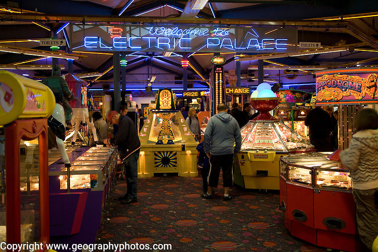 People playing on machines, Electric Palace amusement arcade, Weymouth, Dorset, England