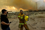 pvcRIOFIRES5/2-23-07/ASEC.  Fire fighters Martin Perea (CQ), right, adjusts his helmet as Mike Ortega (CQ), left, talks to men in the field from an area outside the Fire Department in Rio Communities at NM 47 and 309 while keeping an eye on a wildfire as it closes in on businesses and residences along NM 47, photographed Friday Feb. 23, 2007. (Pat Vasquez-Cunningham/Journal)