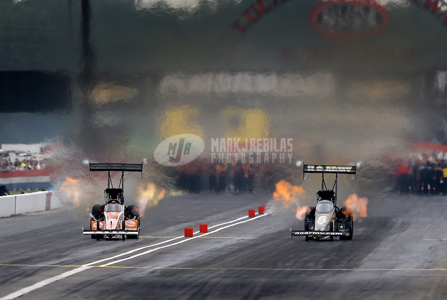 Sept. 2, 2013; Clermont, IN, USA: NHRA top fuel dragster driver Clay Millican (left) races alongside Tony Schumacher during the US Nationals at Lucas Oil Raceway. Mandatory Credit: Mark J. Rebilas-