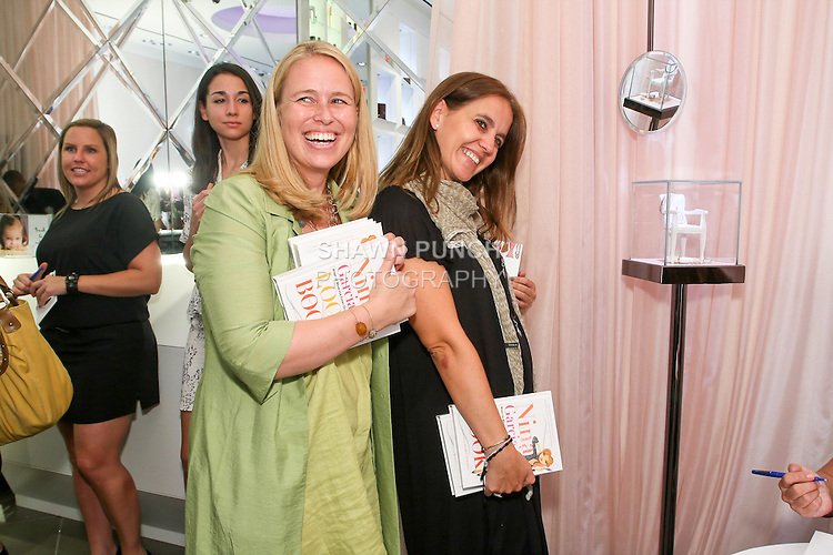 "Guest and Rosa Tous hold books to be signed during Nina Garcia's ""Look Book: What To Wear For Every Occasion"", book release party with Marie Claire at Tous Rockefeller Center, August 17, 2010."
