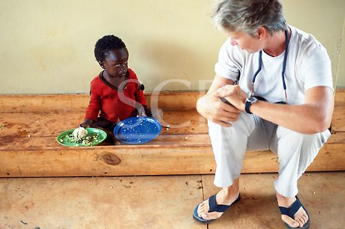 Mbala, Zambia. Female health worker talking to a small boy who is an Aids victim in an orphanage; plates with food.