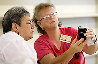 NWA Democrat-Gazette/DAVID GOTTSCHALK  Judges Betsy Garrison (left) and Carol Funk examine a jar of preserves Monday, August 31, 2015 inside the Thompson Hall Adult Home Economics building on the Washington County Fair Grounds in Fayetteville. Eight hundred entries are in the Youth Food Preserve contest iat the fair that begins today and runs through Saturday.