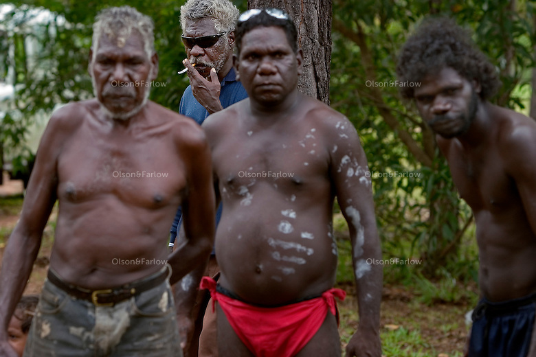 Men line up to watch during a cleansing ceremony on Tiwi Islands.  Body paint seems to be primarily decorative instead of storytelling.  Culture here seems to be more intact because the island is removed from modern western culture.  A cleansing ceremony is the final ceremony in the death of a family member.