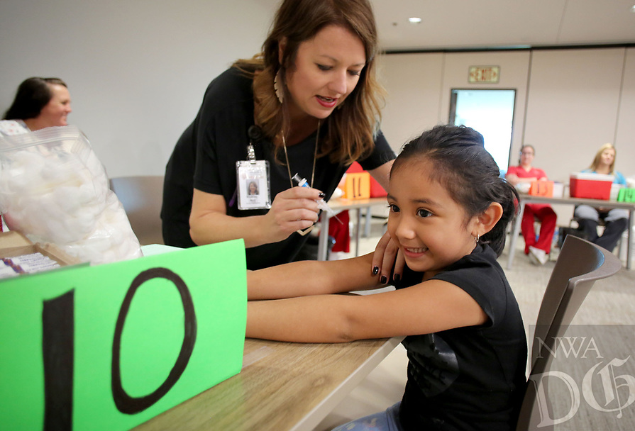 NWA Democrat-Gazette/DAVID GOTTSCHALK  Evangeline Garcia, 3, smiles a she braces Thursday, September 28, 2017, for a flu shot from Whitney Ward, with the Washington County Health Department, during the free flu shot vaccination clinic at the Jones Center in Springdale. The Arkansas Department of Health Benton County Health Unit will hold a flu shot vaccination clinic today at the Rogers Activity Center.