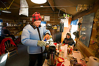 Martin Buser takes a coffee break inside the cabin at Ophir during his 24 hour mandatory layover