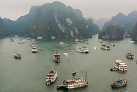 High angle view of ships anchored off Ti top Island in Halong Bay, North Vietnam. The bay features 3,000  limestone and dolomite karsts and islets in various shapes and sizes sprinkled over 1,500 square kilometers. It offers a wonderland of karst topography. It is a UNESCO World Heritage Site.