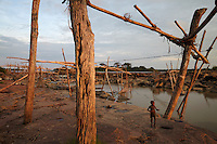A young boy plays among the scaffolds used to support fish traps at Boyoma Falls (known locally as Wagenia Falls). During the dry season water levels are too low for fishing and the oportunity is taken to repair the traps, and the scaffolds that hold them in place. Wagenia is the last of seven cataracts below which the Lualaba River becomes the Congo. For generations members of the Wagenia tribe have built and maintained these structures in the same manner described by Henry Morton Stanley, after whom the falls were also once named, during his navigation of the Congo in 1874-77.
