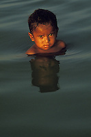 5-years old dark-skinned boy enjoy bathing at a Pantanal lake near Corumba, Mato Grosso do Sul State, Brazil.