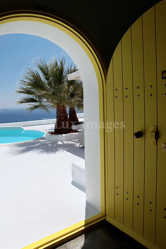 yellow arched door..A 160 sqm house designed by architect, Nicholas Tsebelis, is located in the picturesque village of Oia on the Greek island of Santorini
