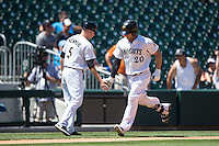 George Kottaras (20) of the Charlotte Knights slaps hands with third base coach Ryan Newman (5) as he rounds the bases after hitting a home run against the Indianapolis Indians at BB&T BallPark on June 21, 2015 in Charlotte, North Carolina.  The Knights defeated the Indians 13-1.  (Brian Westerholt/Four Seam Images)
