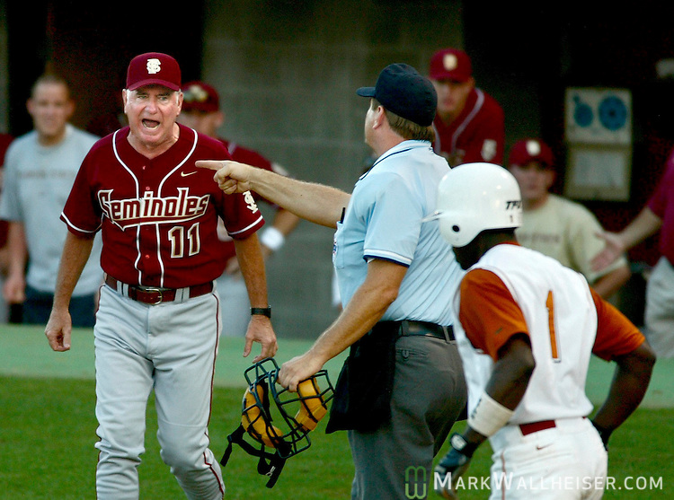 FSU head coach Mike Martin (L) races from the dug out to dispute plate umpire Jeff Henrichs' (C) call to send Texas's second baseman Tim Moss (R) to first on a third strike swing claiming g Moss was hit by the pitch in Tallahassee June 9, 2003.