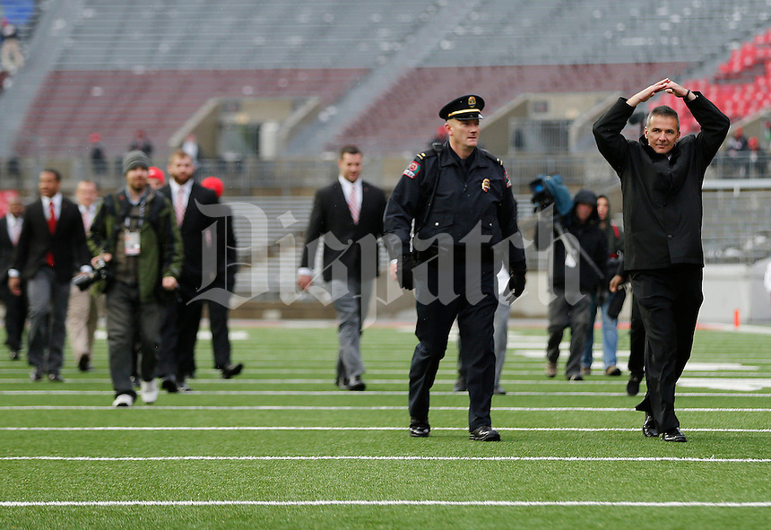 Ohio State Buckeyes head coach Urban Meyer salutes fans as he leads his team on to the field before the college football game between the Ohio State Buckeyes and the Indiana Hoosiers at Ohio Stadium in Columbus, Saturday morning, November 22, 2014. (The Columbus Dispatch / Eamon Queeney)
