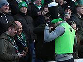 17th March 2019, Dens Park, Dundee, Scotland; Ladbrokes Premiership football, Dundee versus Celtic; Ollie Burke of Celtic tries on a fans St Patricks day hat