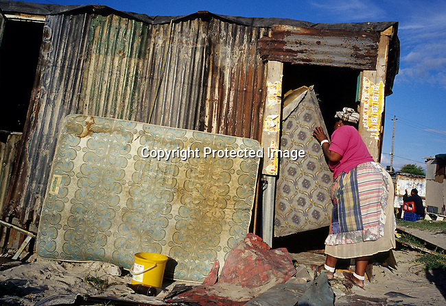 Victoria Mbandazayo, an unemployed woman, carries a mattress inside her newly built shack on October 11, 2003 in Khayelitsha, the biggest black township outside Cape Town, South Africa. She had to move from another nearby location with her four children because the area was destroyed to make place for new housing. It's estimated that over one million people live here, most of them under appalling conditions in shacks with no running water or electricity. The township was founded in 1984. (Photo by: Per-Anders Pettersson).....
