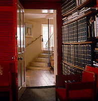 View from the book-lined office to the stairway where a portrait of Lord Snowdon by Bryan Organ hangs above a handrail of gold rope