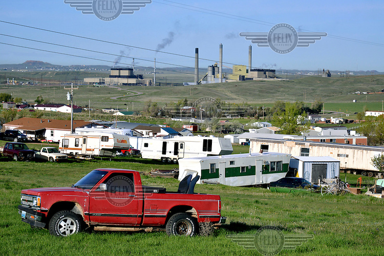Trailer homes with Wyodak coal power station in the background.<br /> <br /> Vast swathes of America's untouched west are being eaten up by development, especially logging and mining and the associated infrastructure, roads and urban growth. Wyoming is the most-affected state, according to a study by the Center for American Progress (CAP). In the decade preceeding 2011 4,300 square miles of Wyoming's wilderness disappeared. The town of Gillette is at the heart of this landscape transformation having grown, alongside the expanding coal industry, from a rural backwater to a town of 31,000.