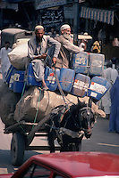 An overworked horse struggles to pull a seriously overloaded cart through the traffic of Peshawar.