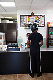 BERMUDA. St. George. Customer ordering food at Art Mel's Spicy Dicy Restaurant in St. George.