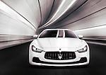 White 2014 Maserati Ghibli S Q4 luxury car speeding in a tunnel. Front view.