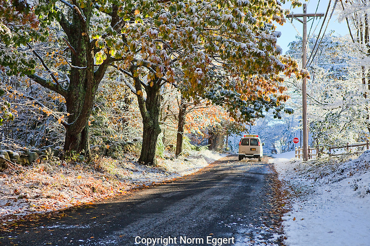 School bus driving along a country road after a late autumn dusting of snow.